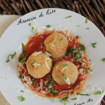 three Baked Rice Balls on a plate with tomato sauce