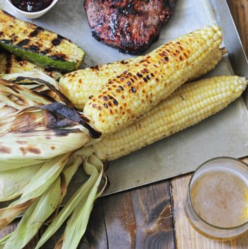 three ears of grilled Corn on the Cob on a table