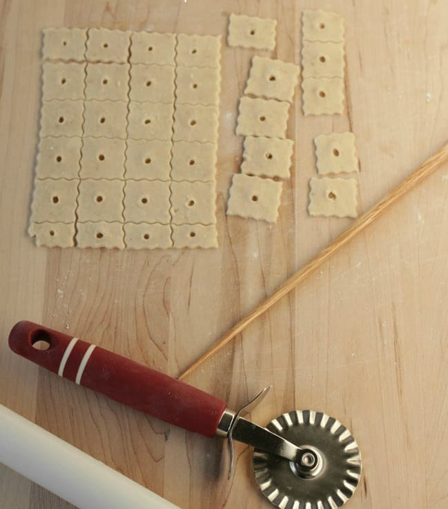 dough on work surface cut into cheez-it shape with pizza cutter
