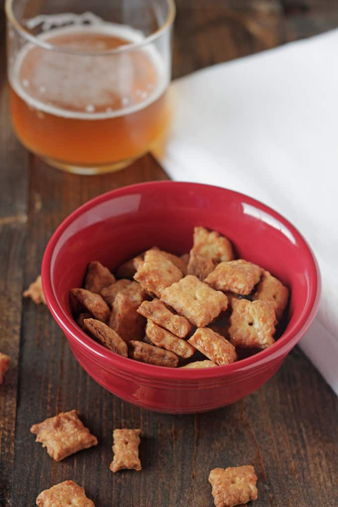 baked homemade cheez-its in a bowl with a glass of beer