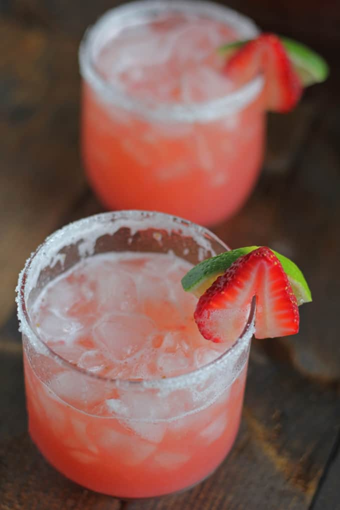 two Strawberry Beer Margarita in a glass with slice of lime and strawberry