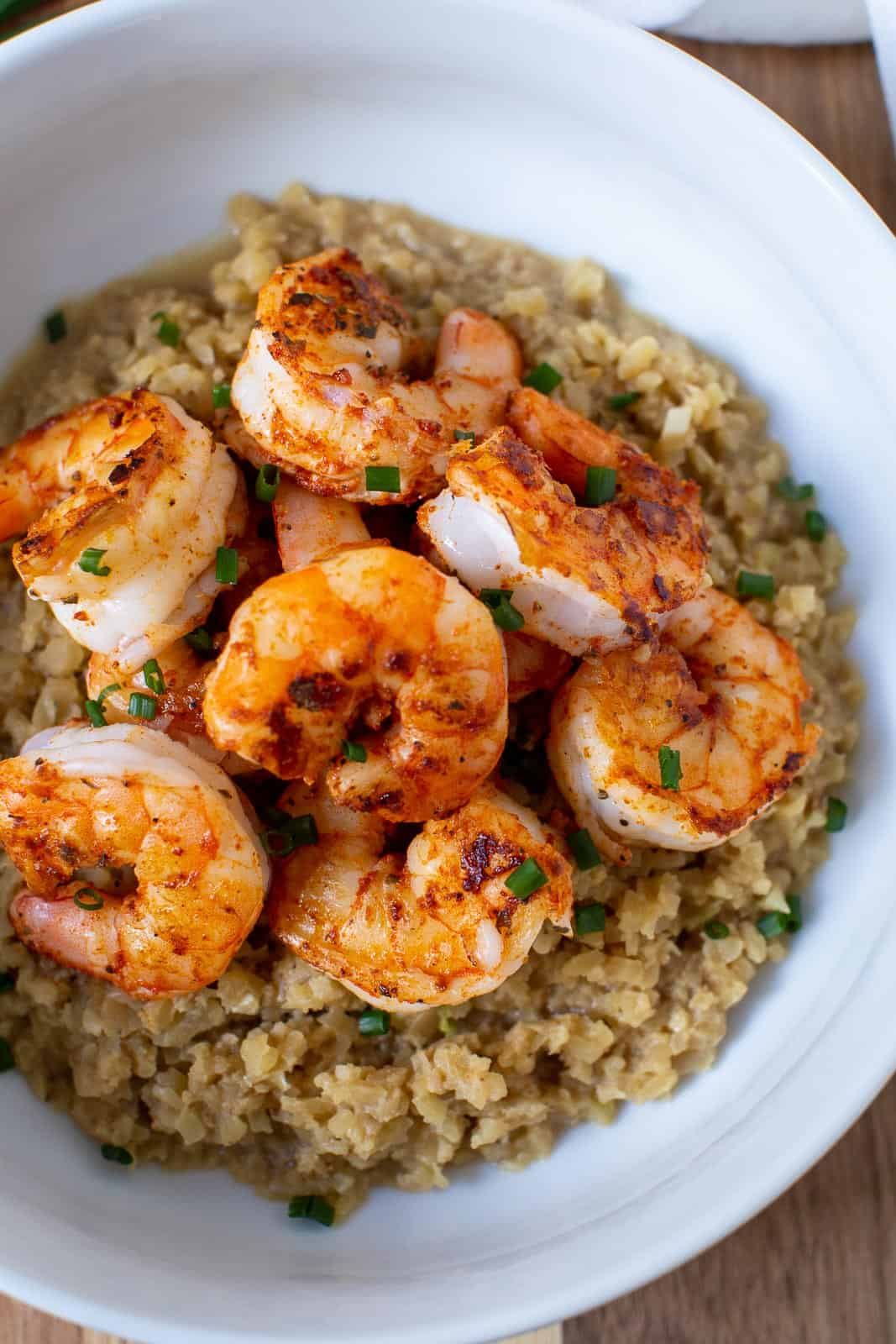white bowl of riced cauliflower with Cajun seasoned shrimp