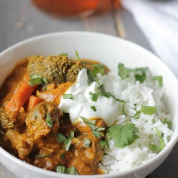 white bowl of Chicken and Vegetable Tikka Masala with white rice on a table