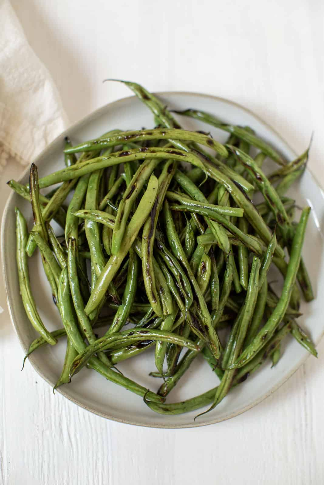 white plate with cooked green beans