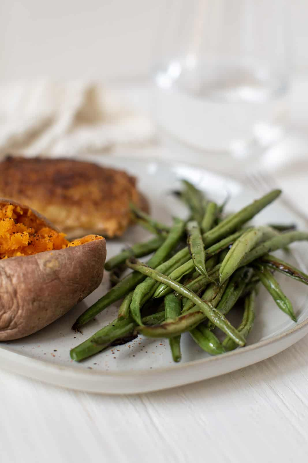 white plate with green beans, sweet potatoes, and roasted chicken.