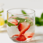 glass of water with basil and strawberries