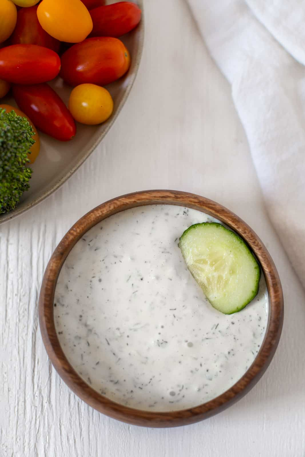 plate of vegetables with bowl of tzatziki sauce with sliced cucmber