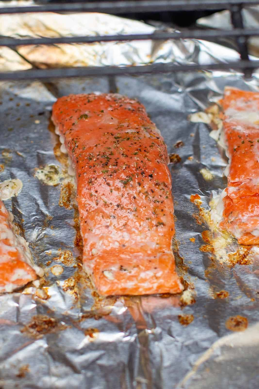 three pieces of salmon cooking on grill