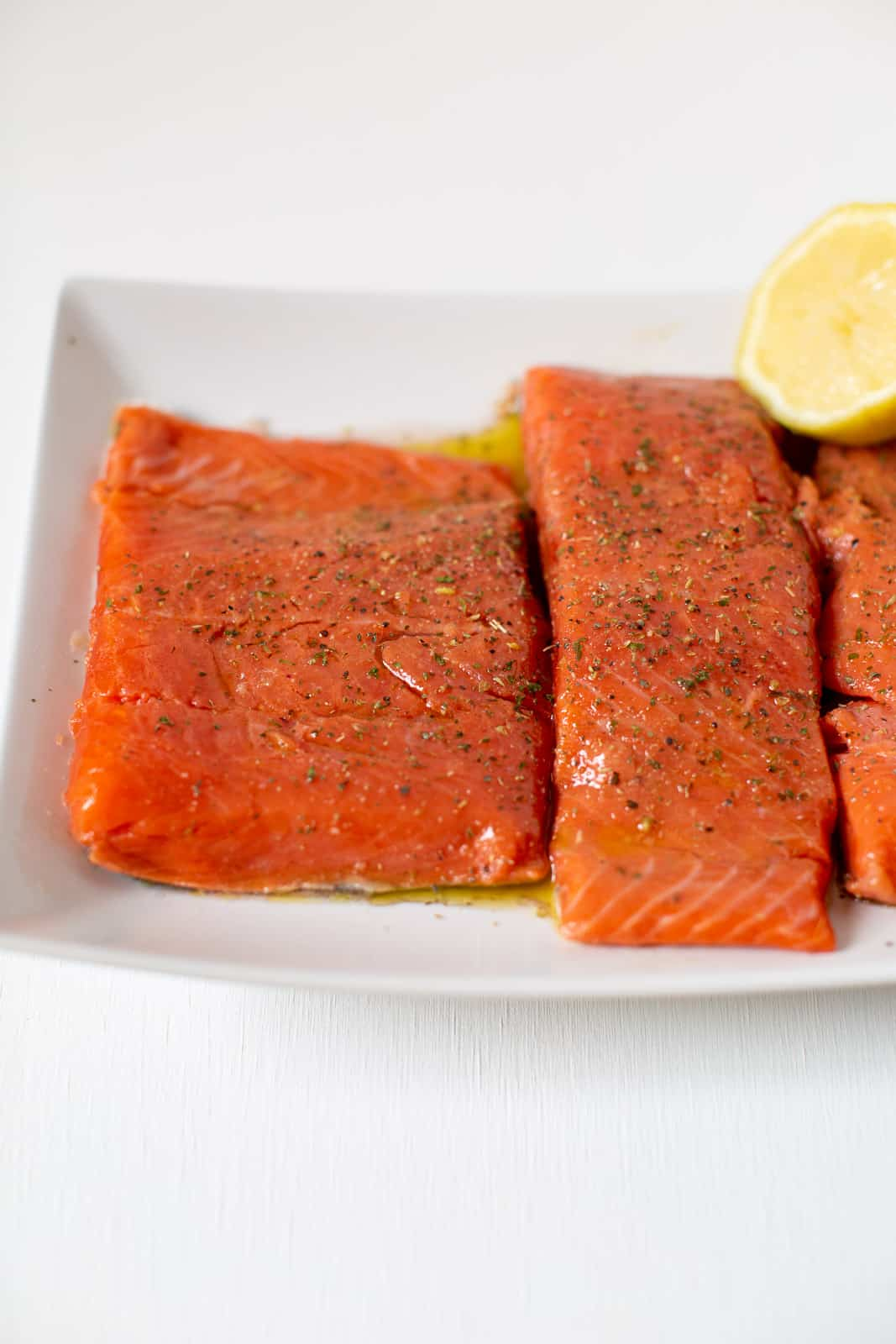 three pieces of raw salmon on a plate