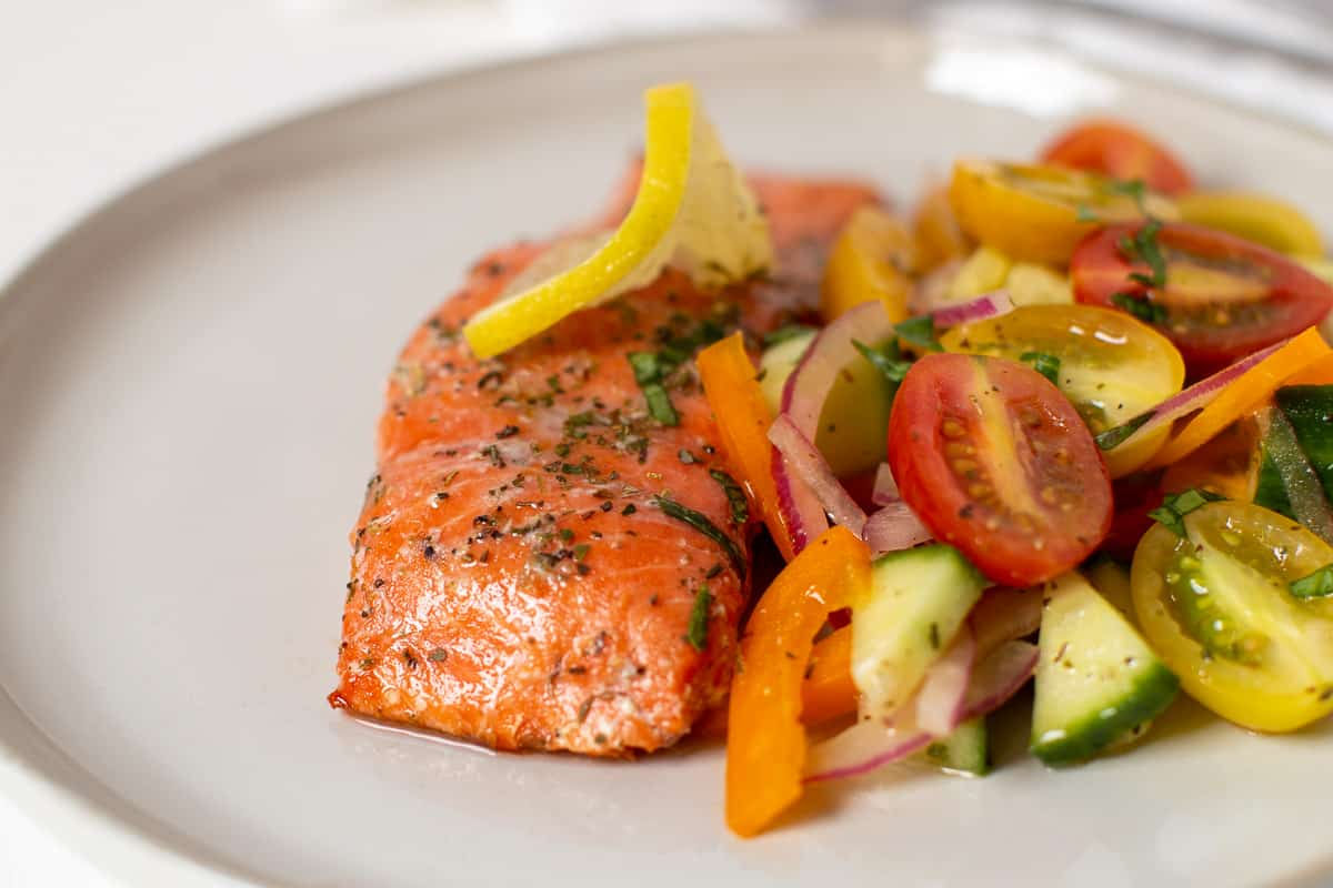 piece of grilled salmon with tomato salad
