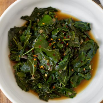 white bowl of cooked collard greens