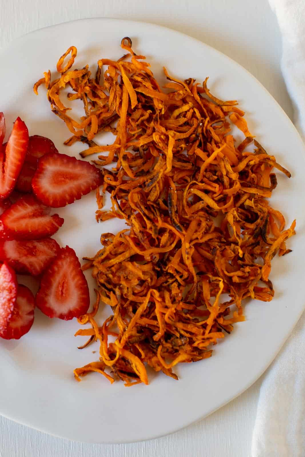 sweet potato hash browns cooked on a plate with strawberries
