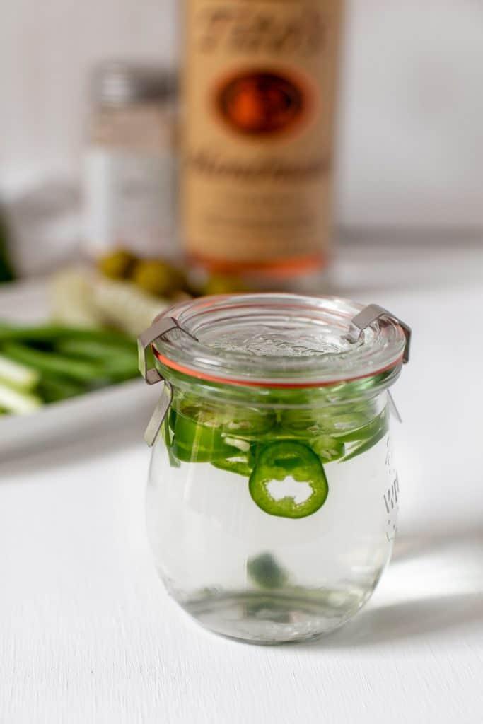 mason jar full of vodka and sliced jalapenos