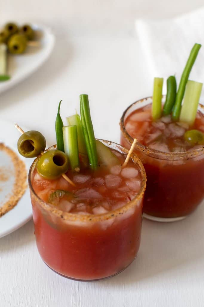 two glasses of bloody mary cocktails with vegetable garnish