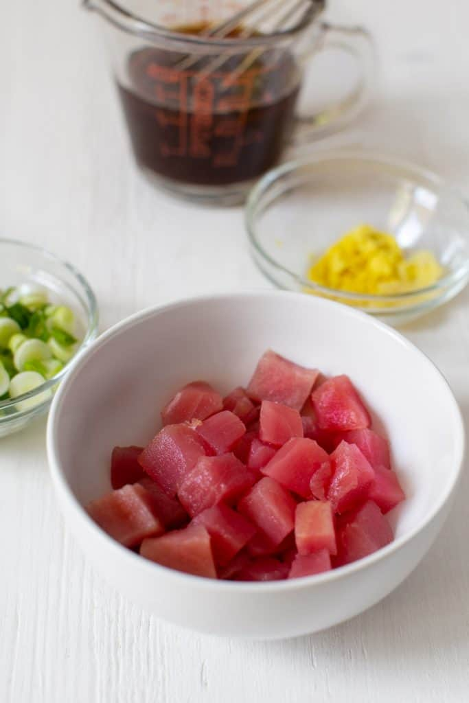 diced ahi tuna in a bowl with ginger and green onions