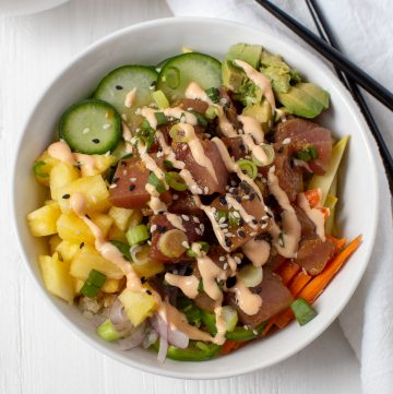 poke bowl with chopped veggies and drizzle of spicy mayo