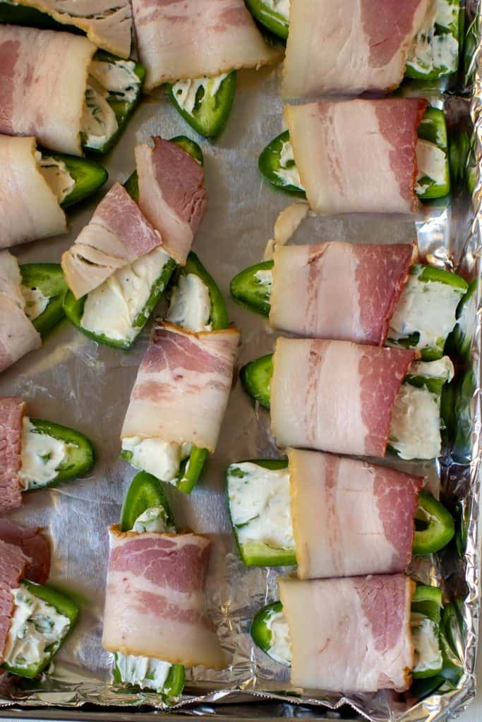 uncooked bacon wrapped jalapeno on a sheet pan