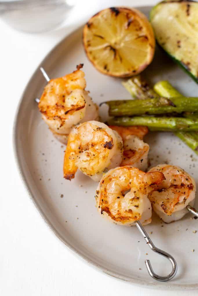 close up of a grilled shrimp on a metal skewer