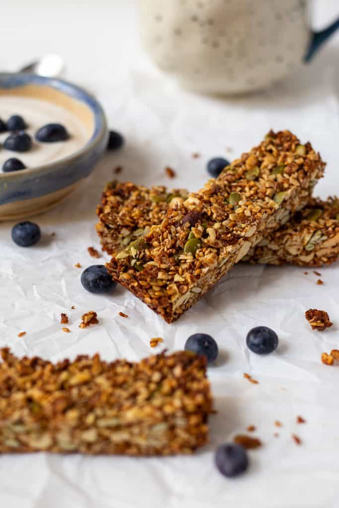 two granola bars on a table with bowl of yogurt