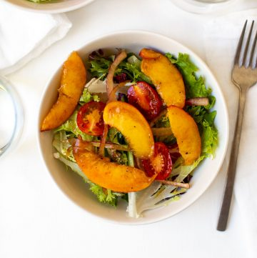 spring mix salad with sliced peaches on the top
