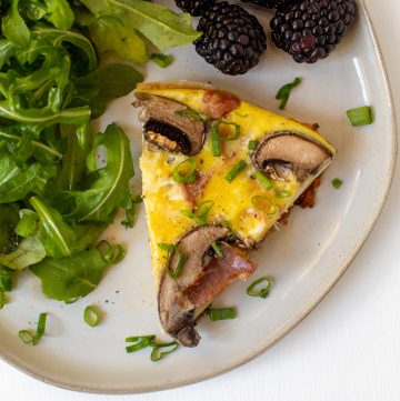 slice of frittata on a plate with mushrooms and prosciutto