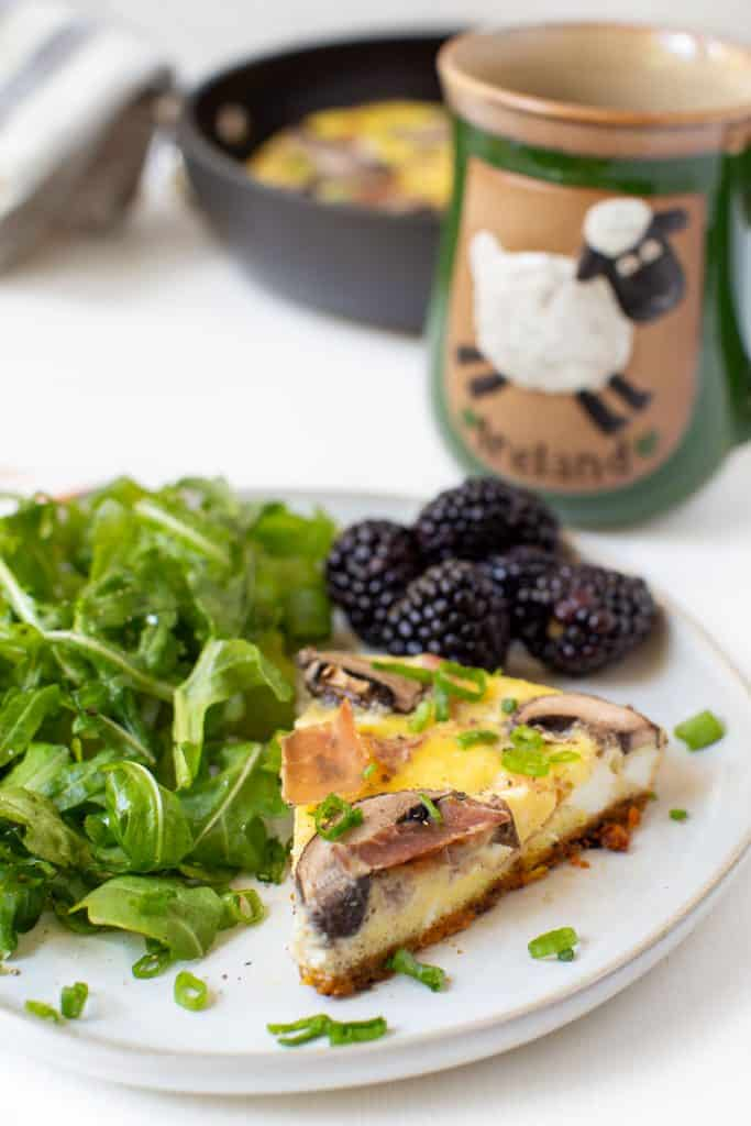 plate of frittata with arugula salad and berries