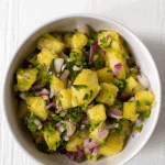 white bowl full of diced pineapple, onion, and jalapeno