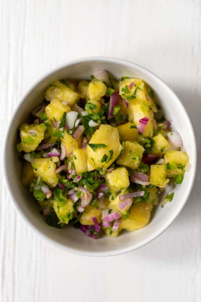 a white bowl full of chopped pineapple, onions, and jalapenos