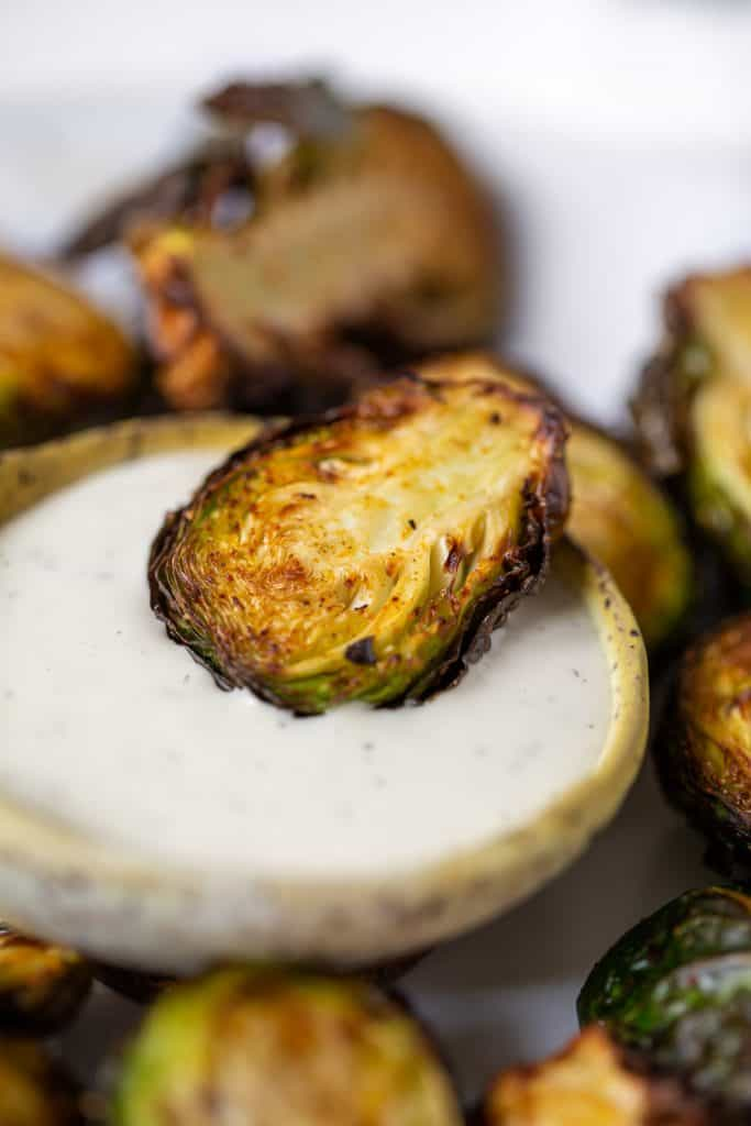 close up of air fried brussels sprout dipped in ranch dressing