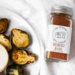 Plate of fried brussels sprouts with jar of The Traveling Spice Co Breakfast Blend