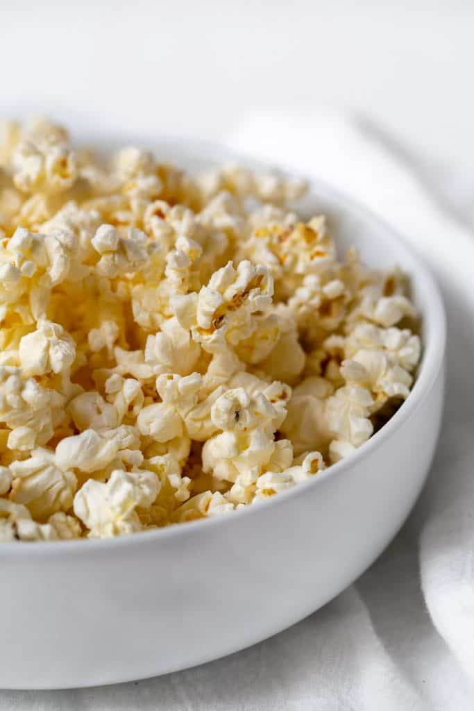 side view of white bowl full of unseasoned microwave popcorn