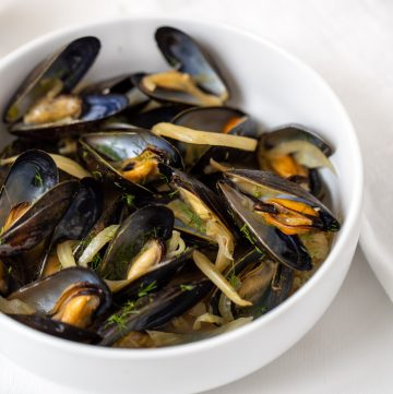 White bowl full of steamed mussels with fennel and onion.