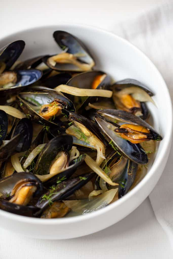 close up of a white bowl full of steamed mussels with fennel and onion.
