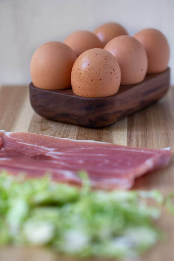 cutting board with whole eggs, sliced prosciutto, and shredded brussels sprouts