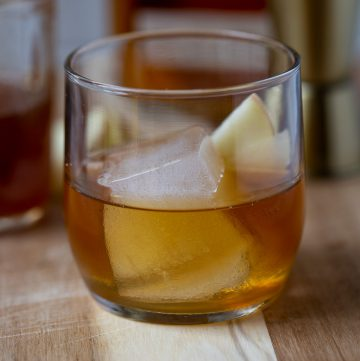 close up of cinnamon old fashioned on a table with sliced apples