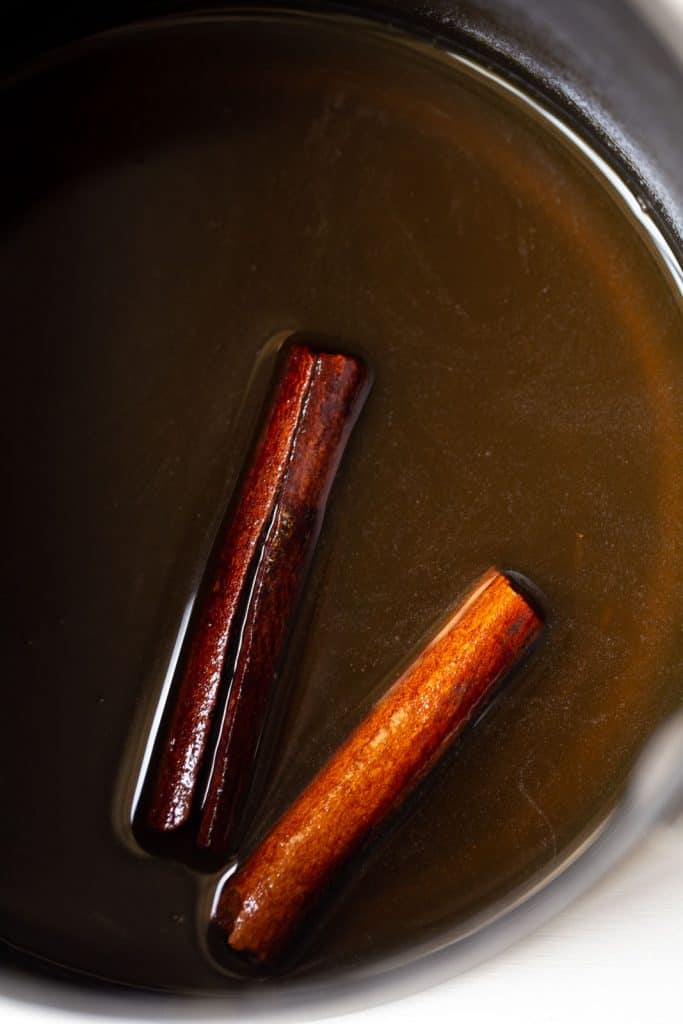 two cinnamon sticks in a sauce pan with honey and water.