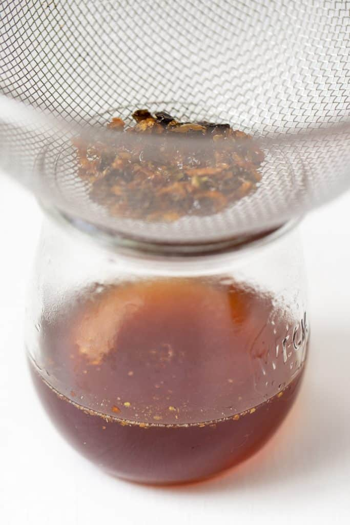 pepper flakes in a strainer over hot honey in a bowl