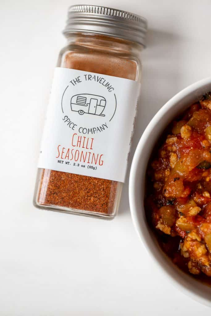 bowl of paleo chili with jar of The Traveling Spice Co Chili Seasoning