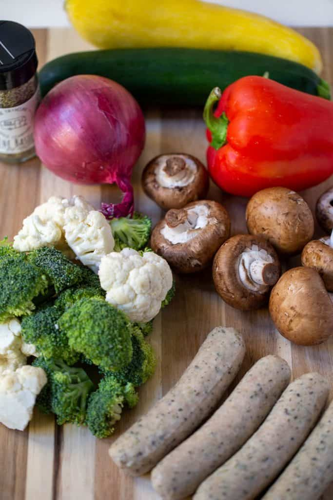 cutting board with sausage, mushrooms, onion, and broccoli.