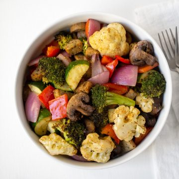 white bowl full of roasted vegetables and sausage