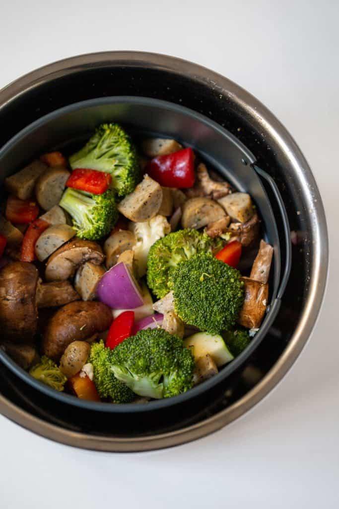 air fryer basket full of veggies and sausage.