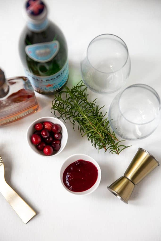 photo of ingredients for Cranberry and Bourbon Cocktail - bourbon, cranberry sauce, rosemary sprig, and glasses.