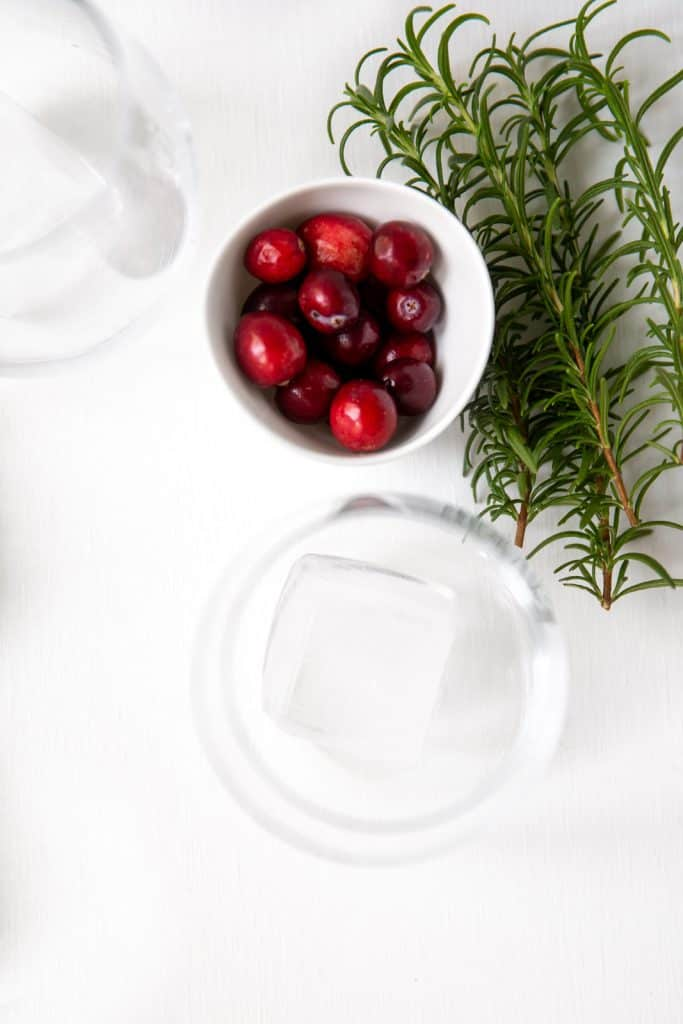 Close up of cocktail glass and small bowl of whole cranberries with sprig of rosemary.