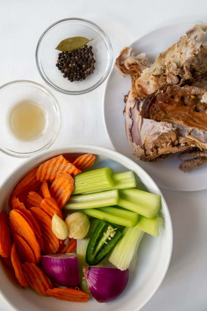 photo of all the ingredients used to make bone broth. Turkey bones, veggies, spices, and apple cider vinegar.