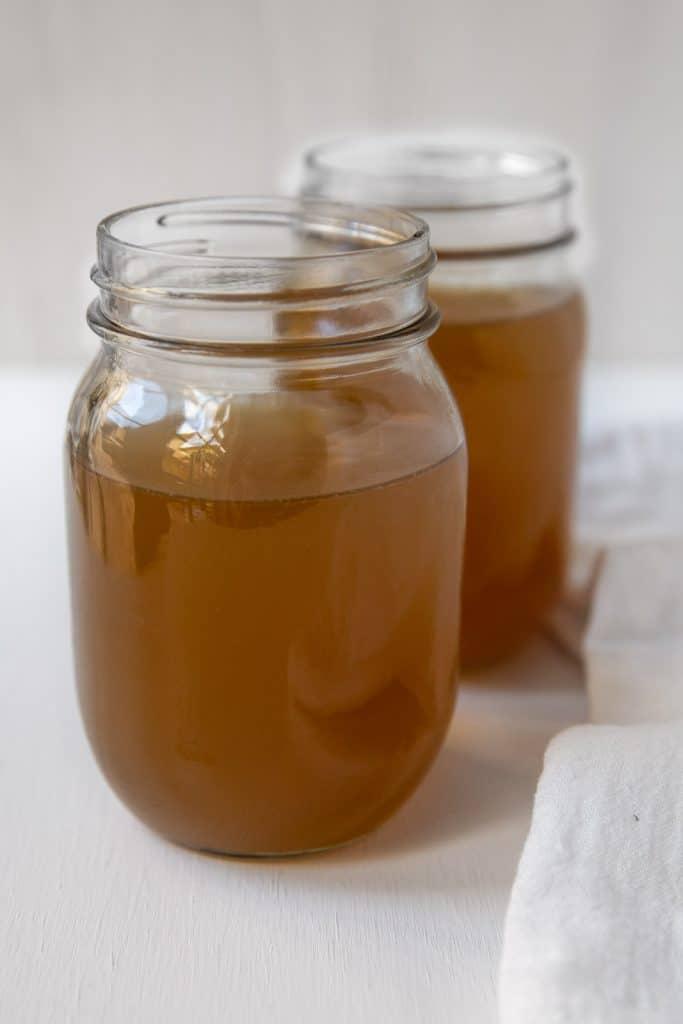 close up of Two mason jars full of turkey bone broth