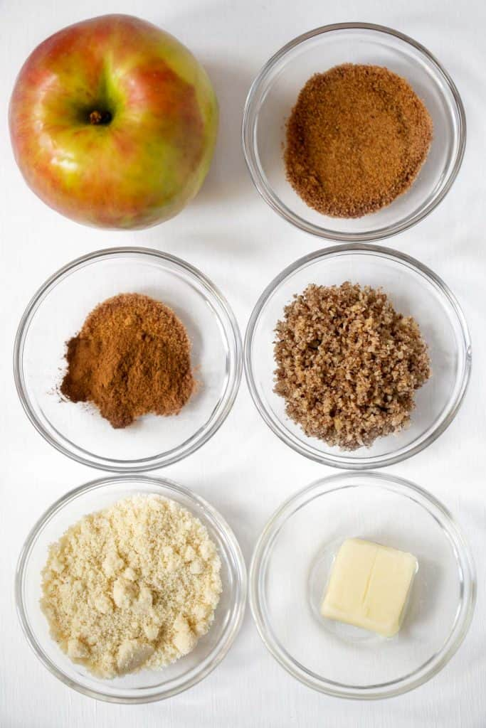 photo of all the ingredients in the paleo apple crisp. From the top: apple, coconut sugar, cinnamon, pecans, almond flour, and butter.