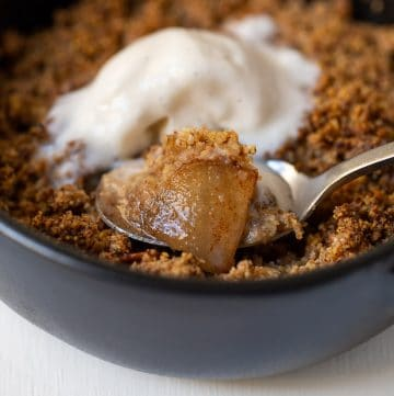 close up of a spoon full of apple crisp with ice cream.