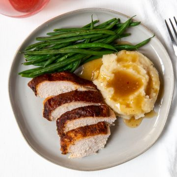 overview of a plate with green beans, smoked turkey, and mashed potatoes and gravy
