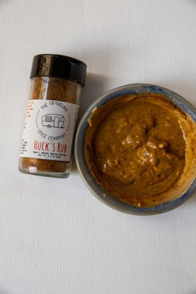 close up of a jar of Huck's Rub seasoning and a bowl of seasoning and butter formed into a paste.