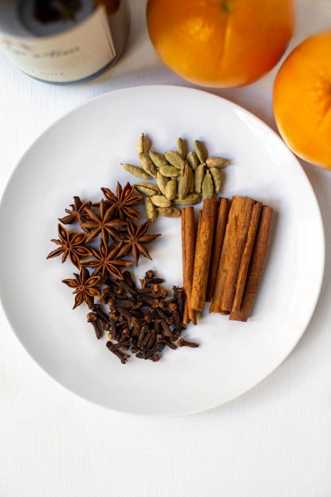 Plate with whole cinnamon sticks, cloves, star anise, and cardamom.